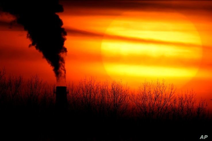 FILE - In this Monday, Feb. 1, 2021 file photo, emissions from a coal-fired power plant are silhouetted against the setting sun…