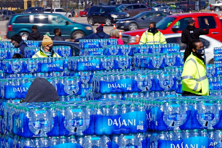 Water is loaded into cars at a City of Houston water distribution site Friday, Feb. 19, 2021, in Houston. The drive-thru...