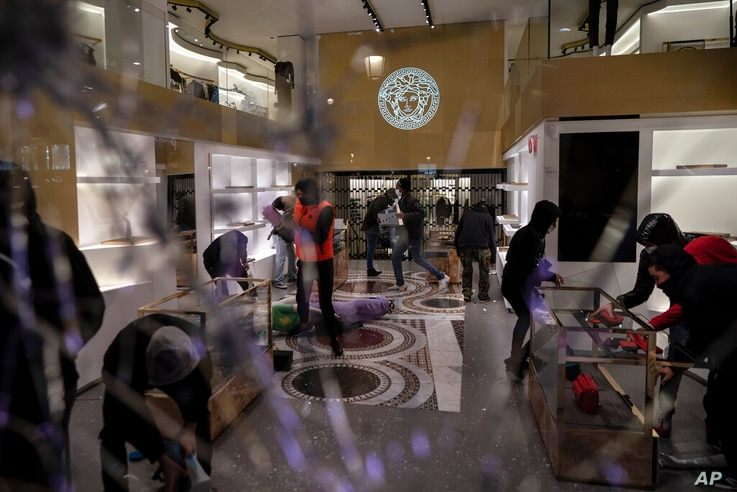 People loot a Versace store during a protest condemning the arrest of rap singer Pablo Hasel in Barcelona, Spain, Saturday, Feb...