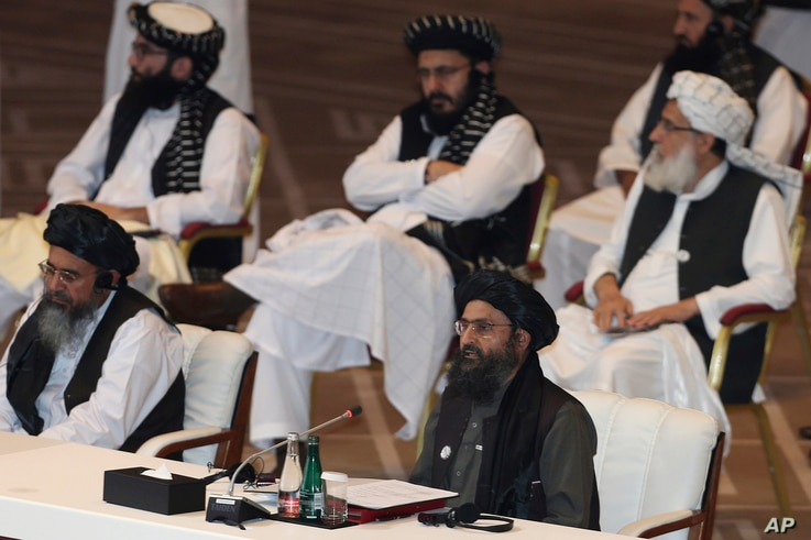 FILE - In this Sept. 12, 2020, file photo, Taliban co-founder Mullah Abdul Ghani Baradar, bottom right, speaks at the opening...
