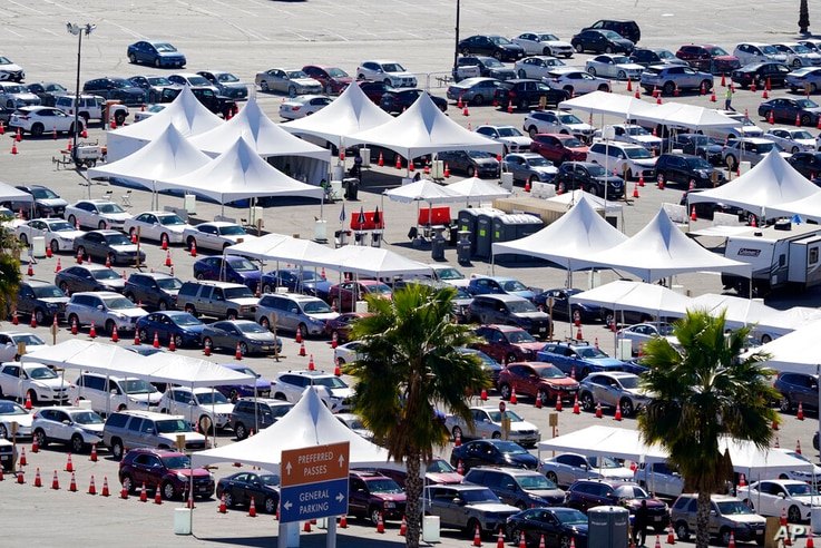 Motorists line up at a COVID-19 vaccination site at Dodger Stadium Tuesday, Feb. 23, 2021, in Los Angeles. (AP Photo/Marcio…