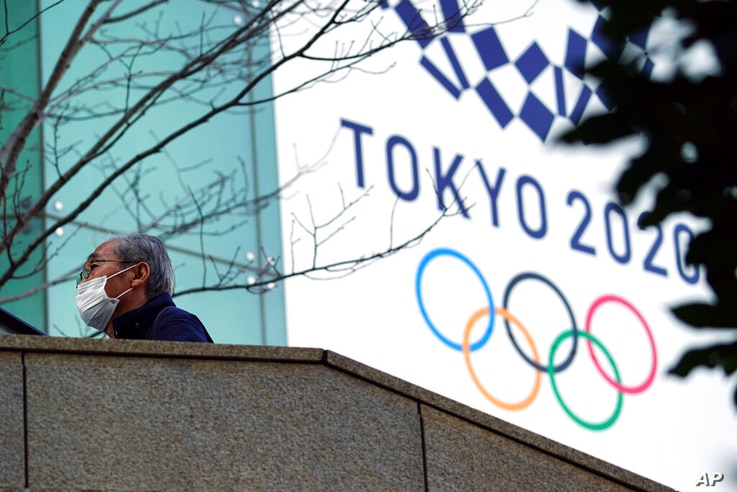 A man wearing a protective mask to help curb the spread of the coronavirus walks near the banner for the Tokyo 2020 Olympic…