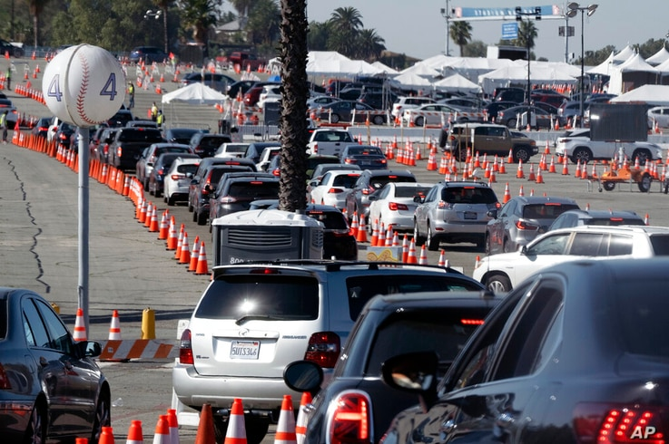 Cars wait in line as they enter a COVID-19 vaccination site at Dodger Stadium in Los Angeles, on Thursday, Feb. 25, 2021. (AP…