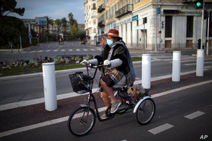 Nice resident Noel and her dog Glugi go for a bike ride during confinement in Nice, southern France, Saturday, Feb. 27, 2021…