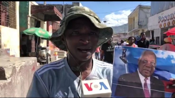 A protester in the Solino neighborhood of Port au Prince holds a photo of Supreme Court Justice Joseph Mécène Jean Louis. (VOA/Matiado Vilme)