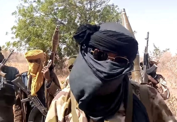 Shehu Rekep, deputy of a bandit gang in Nigeria's Zamfara state, conceals his face with a scarf and sunglasses.