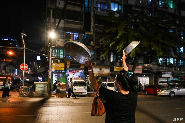 A woman clatters pans to make noise after calls for protest went out on social media in Yangon as Myanmar's ousted leader Aung San Suu Kyi was formally charged two days after she was detained in a military coup.