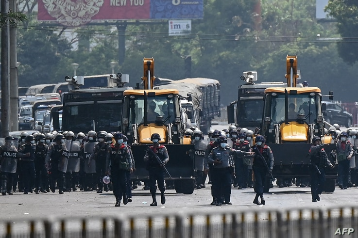 Police advance in heavy construction equipment towards protesters demonstrating against a military coup in Yangon, Myanmar, February 22, 2021.