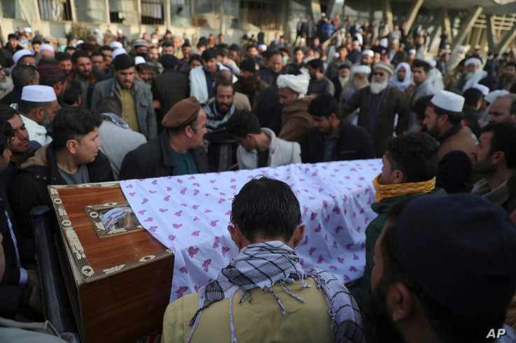 FILE - Afghans carry the coffin of a victim of a bombing and shooting attack, during his funeral, in Kabul, Afghanistan, Dec. 23, 2020.