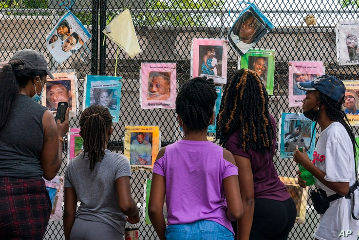 Melissa Brooks, from left, Jordan Brown, Jazmine Brooks, Shari Moore and and Laila Brooks, all of Baltimore, study photographs of Black people killed by police that cover a fence near the White House, Washington, Aug. 25, 2020.