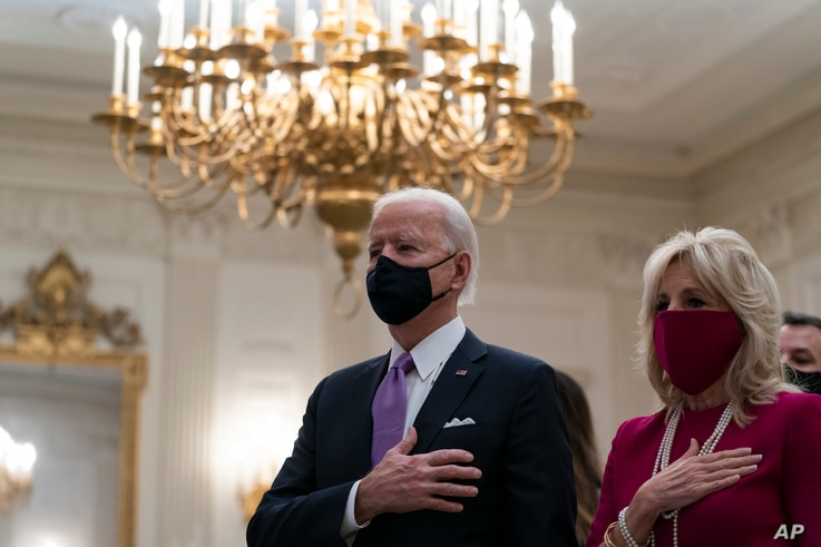 FILE - U.S. President Joe Biden, accompanied by first lady Jill Biden, places his hand over his heart during a virtual Presidential Inaugural Prayer Service in the State Dinning Room of the White House, in Washington, Jan. 21, 2021.