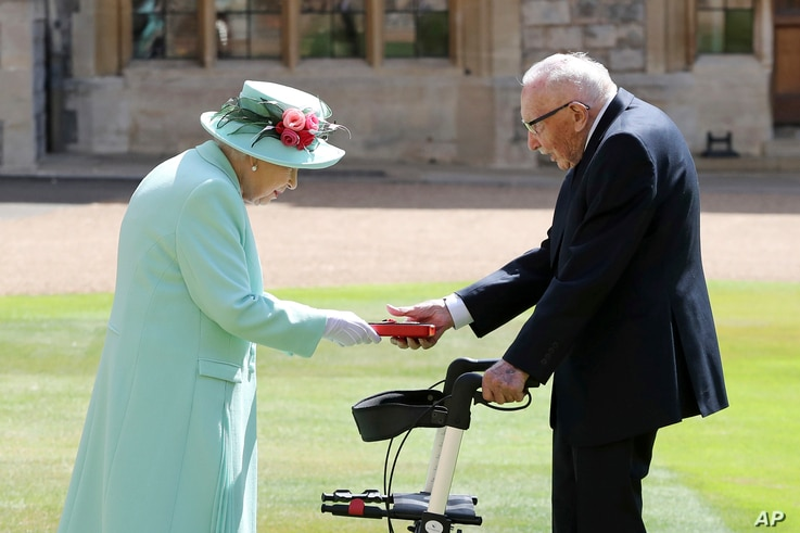 FILE - Captain Sir Thomas Moore receives his knighthood from Britain's Queen Elizabeth, during a ceremony at Windsor Castle in Windsor, England, July 17, 2020.