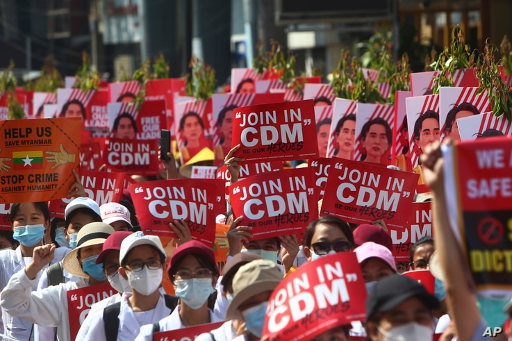 Anti-coup protesters hold up signs calling on others to join the CDM (Civil Disobedience Movement) during a rally near the Mandalay Railway Station in Mandalay, Myanmar, Feb. 22, 2021.