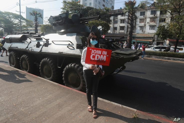 """An anti-coup protester holding a sign reading """"Join in CDM (Civil Disobedience Movement)"""" poses for a photo in front of an armored personnel carrier deployed outside the Central Bank of Myanmar building, in Yangon, Myanmar, Feb. 15, 2021."""