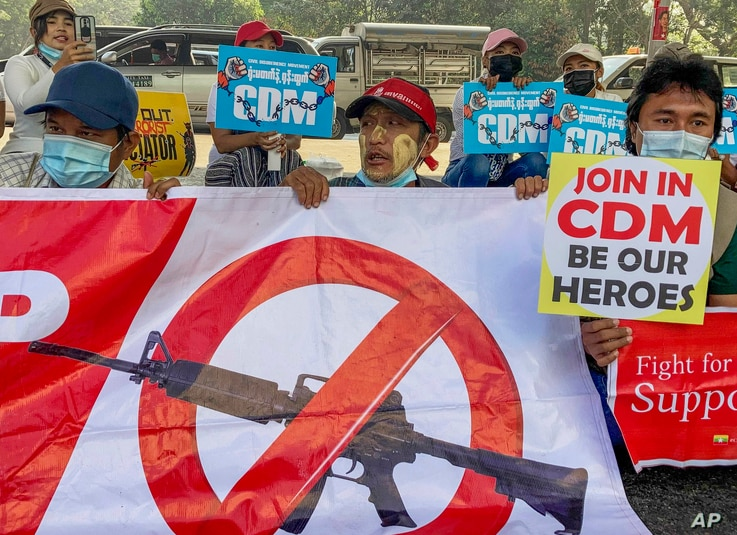Anti-coup protesters hold up signs in support of Myanmar's Civil Disobedience Movement, during a rally in Yangon, Myanmar, Feb. 24, 2021.