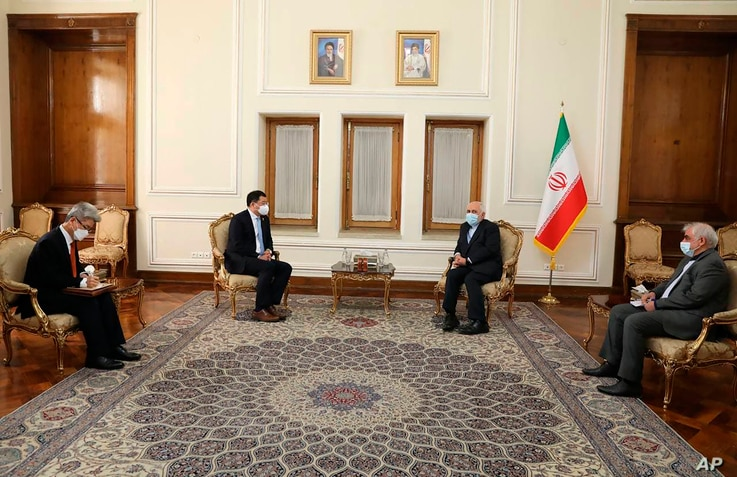 In this photo released by the Iranian Foreign Ministry, South Korean Vice Foreign Minister Choi Jong Kun, center left, speaks with Iranian Foreign Minister Mohammad Javad Zarif, center right, during their meeting in Tehran, Jan. 11, 2021.