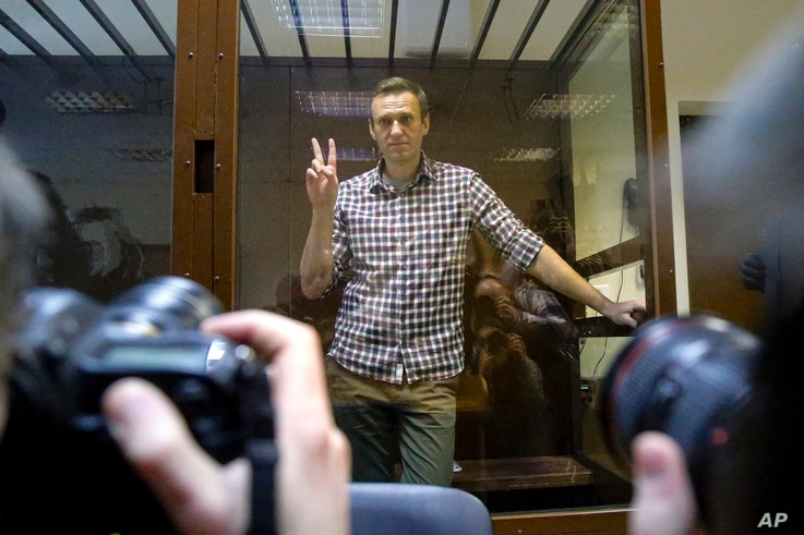 Russian opposition leader Alexey Navalny gestures as he posed for photographers standing in a glass enclosure at the Babuskinsky District Court in Moscow, Russia, Feb. 20, 2021.