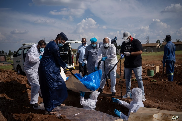 Family members and volunteers from the Saaberie Chishty Society lower the body of a COVID-19 victim into a grave at the Avalon cemetery in Lenasia, South Africa, Jan. 4, 2021.