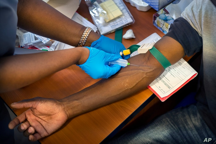 FILE - Blood is drawn from a clinical trials patient for the AstraZeneca test vaccine at the a hospital facility outside Johannesburg, South Africa, Nov. 30, 2020.