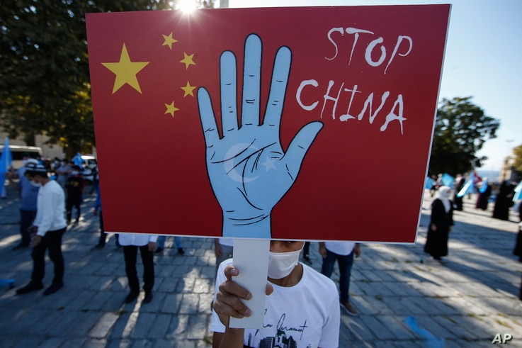 FILE - A protester from the Uighur community living in Turkey holds up an anti-China placard during a protest in Istanbul, Turkey, Oct. 1, 2020. A new Freedom House report says that China's alleged repression of Uighurs extends beyond its borders.