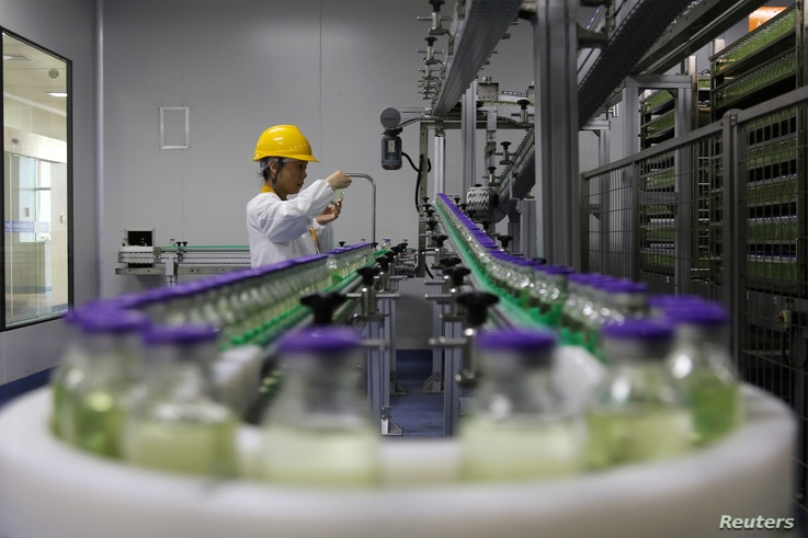 FILE - An employee works on a production line manufacturing drugs at the Yangtze River Pharmaceutical Group in Taizhou, Jiangsu province, China, Sept. 3, 2019.