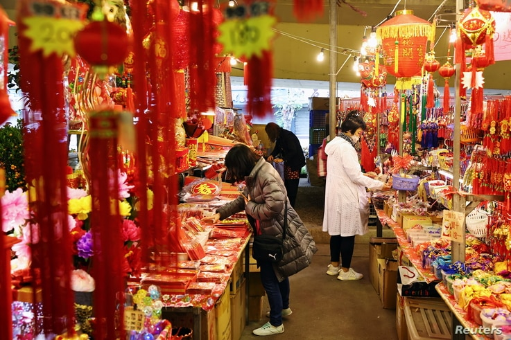 FILE - People wearing masks to protect against the coronavirus shop ahead of the Lunar New Year holiday, in Taipei, Taiwan, Feb. 9, 2021. Taiwanese returning home to shelter from the pandemic have provided an unexpected boost for the island's economy.