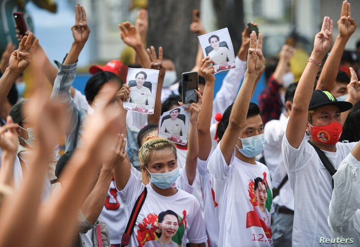 Myanmar citizens show the three-finger salute during a protest against the military coup in Myanmar outside United Nations venue in Bangkok, Thailand, Feb. 7, 2021.