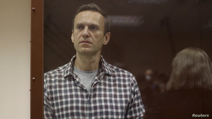 Kremlin critic Alexei Navalny stands inside a defendant dock during a court hearing in Moscow, Russia, Feb. 20, 2021, in this still image taken from video.