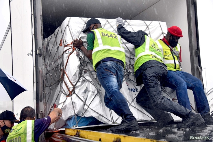 Workers load South Africa's first COVID-19 vaccine as they arrive at OR Tambo airport in Johannesburg, Feb. 1, 2021.