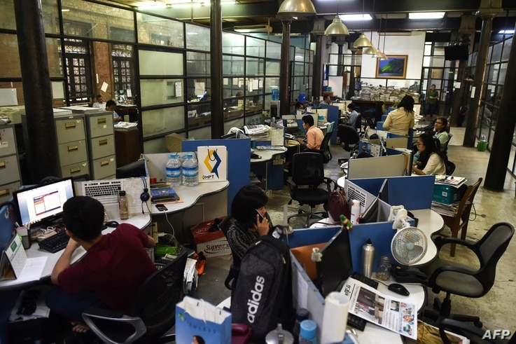 Journalists work in the newsroom of privately owned Myanmar Times newspaper in Yangon on October 11, 2018. (Photo by YE AUNG…