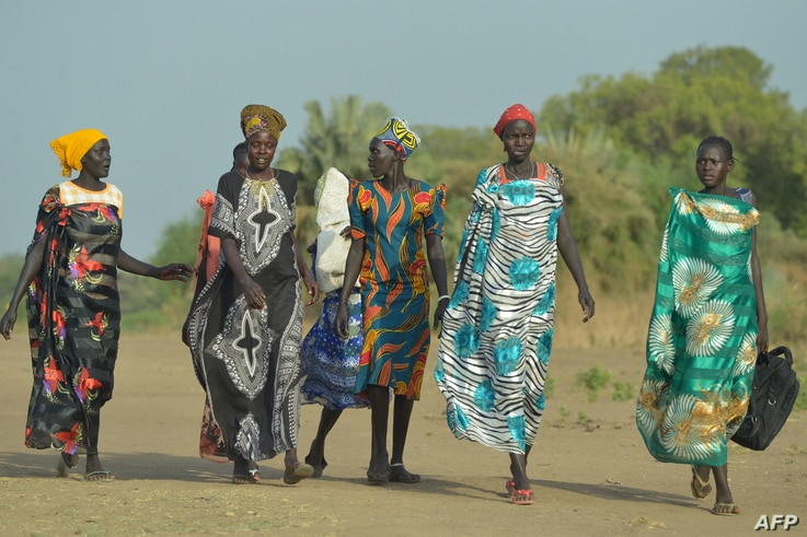 Women walk to the market in Udier town, in South Sudan on March 7, 2019. (Photo by SIMON MAINA / AFP)