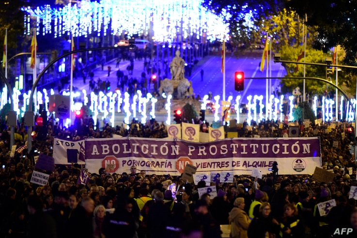 """Women hold a giant banner reading """"Abolition of prostitution"""" during a demonstration to mark the International Day for the…"""