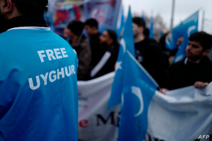 Demonstrators take part in a protest outside the Chinese embassy in Berlin on December 27, 2019, to call attention to China's…