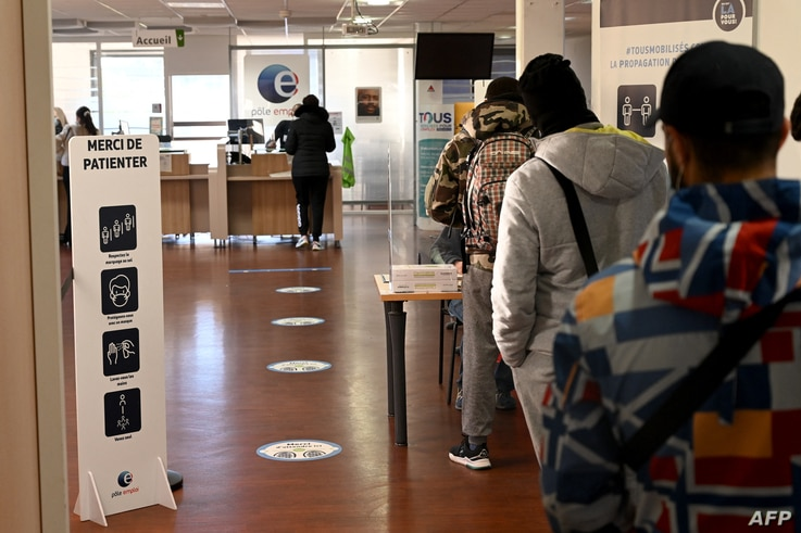 People stand in line at the 'Pole Emploi' agency of Chateau-Gombert in Marseille, southern France, on December 14, 2020. (Photo…
