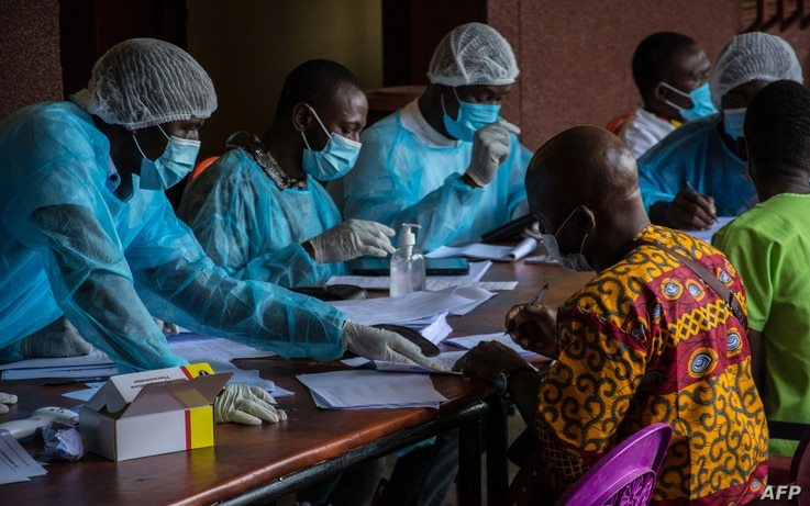 Health workers from the Guinean Ministry of Health prepare forms to register medical staff ahead of their anti-ebola vaccines...
