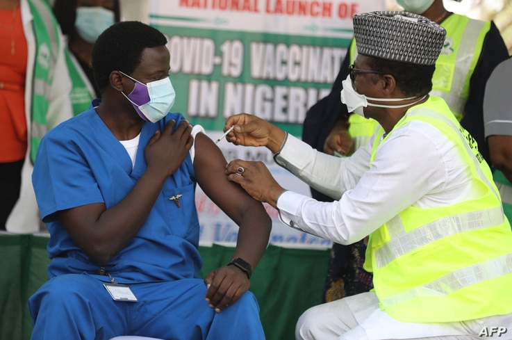 Dr. Ngong Cyprian (L), the first Nigerian to receive the first dose of the Oxford/AstraZeneca vaccine at the National Hospital…