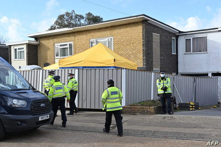Police officers are seen in front of temporary barriers at a home in Deal, southeast England, on March 12, 2021 as officers…