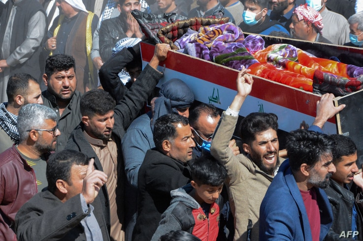 Iraqi mourners carry a coffin at the funeral of eight people killed a day earlier in attacks claimed by the Islamic State (IS)…