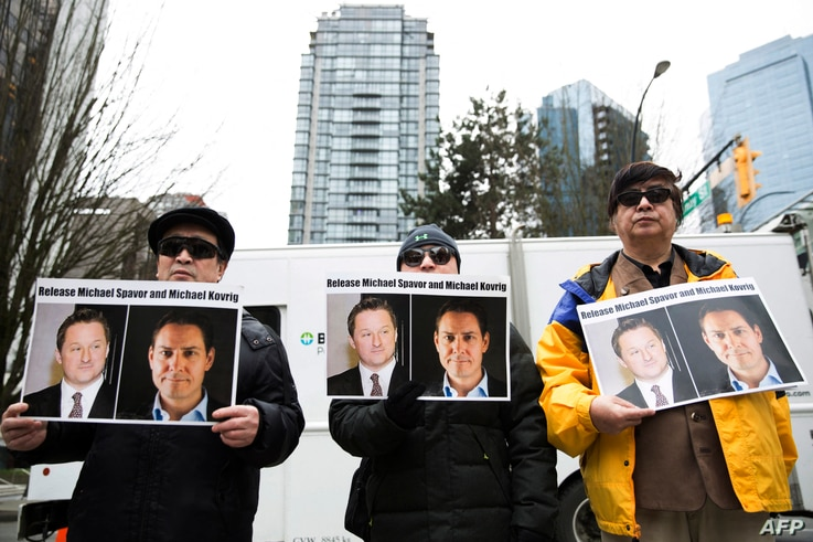 (FILES) In this file photo taken on March 06, 2019, protesters hold photos of Canadians Michael Spavor and Michael Kovrig, who...
