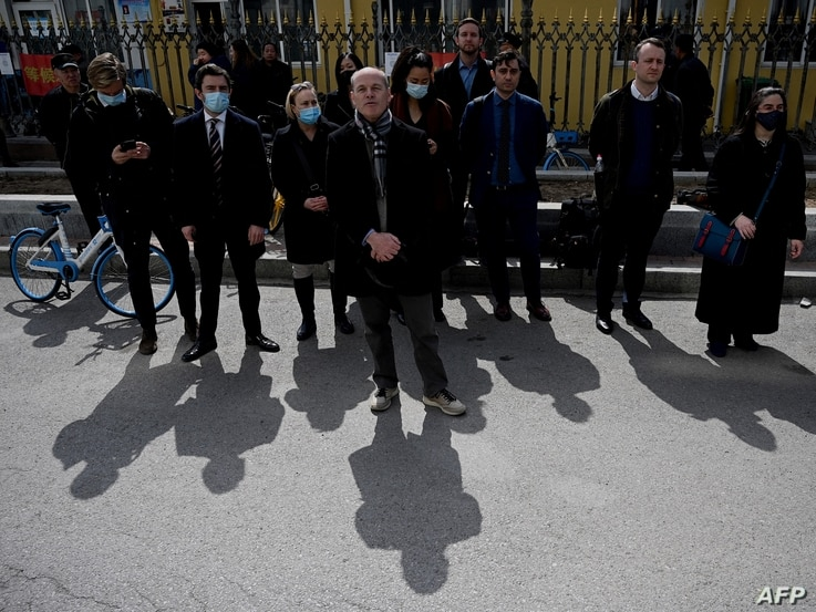 Diplomats from various countries including Jim Nickel (C), deputy head of mission of the Canadian embassy in Beijing, wait...
