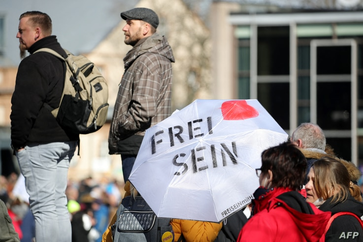 Protestors hold up an umbrella with the lettering reading 'Be free' as they gather for a demonstration to demand the compliance…
