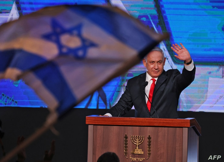 Israeli Prime Minister Benjamin Netanyahu, leader of the Likud party, waves to supporters at the party campaign headquarters in…