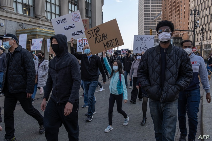 People march during a 'Stop Asian Hate' rally in downtown Detroit, Michigan on March 27,2021, as part of  a nation wide protest…