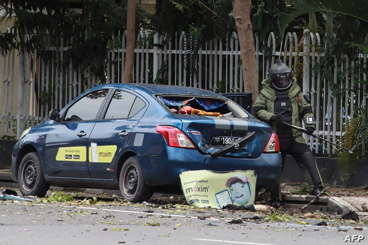 An Indonesian anti-bomb unit (C) collects evidences after a bomb exploded in Makassar on March 28, 2021. (Photo by IRVAN…