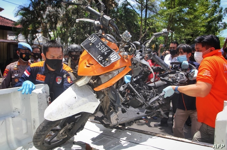 Indonesian police remove a motorcycle that was used by bombers during a reconstruction of the explosion in Makassar on March 29…
