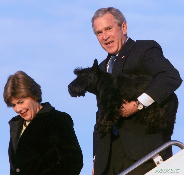 U.S. President George W. Bush holds his pet, Barney, as he and first lady Laura Bush walk down the ramp from Air Force One…