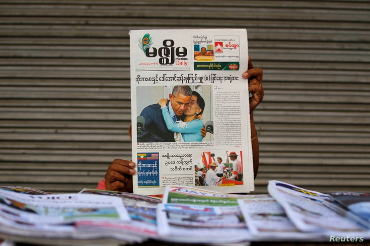 A woman shows a Mizzima newspaper with a photograph of U.S. President Barack Obama and Myanmar pro-democracy leader Aung San…