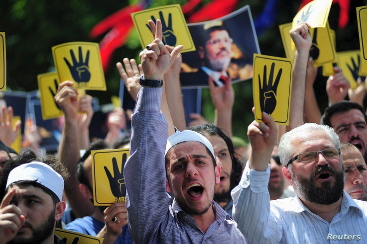 Pro-Islamist demonstrators shout slogans in favour of former Egyptian President Mohamed Mursi and hold signs that show the…