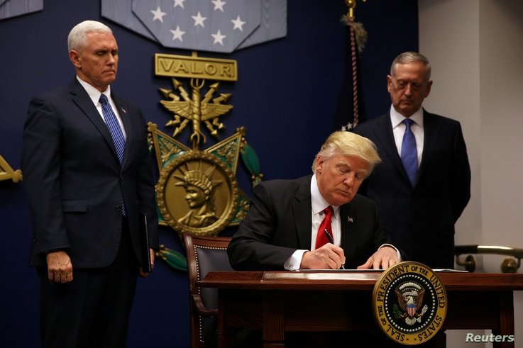 U.S. President Donald Trump signs an executive order he said would impose tighter vetting.