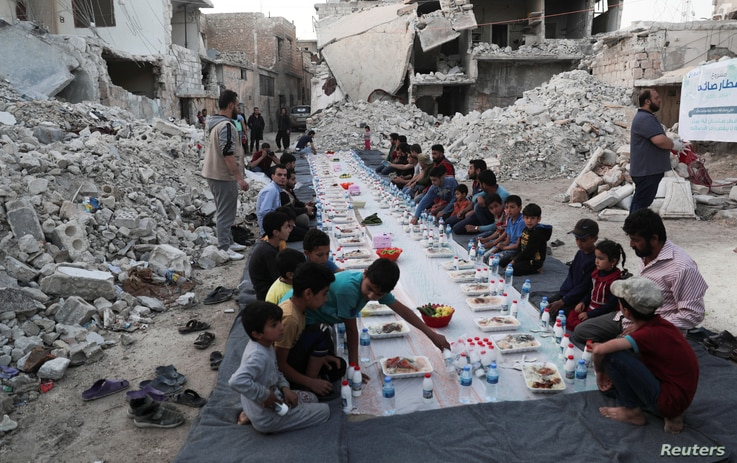 People wait the call to prayer before they eat their Iftar meal provided by a group of volunteers, in a damaged neighbourhood,…